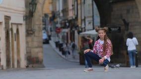 Κορίτσι που κάθεται οκλαδόν στην οδό στο υπόβαθρο bokeh απόθεμα βίντεο