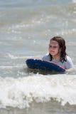 Κορίτσι που κάνει σερφ τα κύματα στον ωκεανό σε έναν πίνακα boogy στοκ εικόνες με δικαίωμα ελεύθερης χρήσης