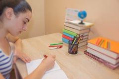 κορίτσι που κάνει τα μαθήματα στο σπίτι Στοχαστική συνεδρίαση νέων κοριτσιών στα des Στοκ φωτογραφίες με δικαίωμα ελεύθερης χρήσης
