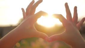 Κορίτσι που κάνει τα χέρια καρδιών ενάντια στον ουρανό, χέρια παιδιών που διαμορφώνουν μια μορφή καρδιών με τη σκιαγραφία ηλιοβασ απόθεμα βίντεο