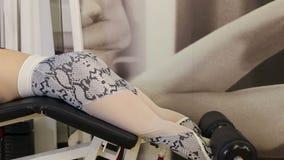 Κορίτσι που κάνει την άσκηση για τα πόδια σε μια μηχανή Τύπου στη γυμναστική απόθεμα βίντεο