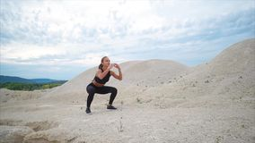 Κορίτσι που κάνει την άσκηση στάσεων οκλαδόν κατά τη διάρκεια του workout έξω από την πόλη απόθεμα βίντεο
