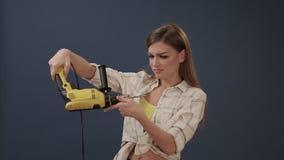 Κορίτσι που κάνει την επισκευή που κρατά ένα τρυπάνι στα χέρια της απόθεμα βίντεο