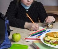 Κορίτσι που κάνει την εργασία και που τρώει τους ξηρούς καρπούς στοκ εικόνα με δικαίωμα ελεύθερης χρήσης