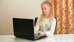 Κορίτσι που κάνει την εργασία που χρησιμοποιεί το lap-top φιλμ μικρού μήκους