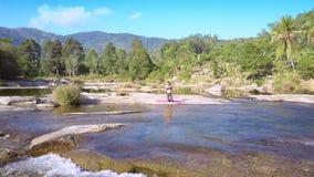 Κορίτσι που κάνει τη γιόγκα στην πέτρα ενάντια στον ποταμό βουνών φιλμ μικρού μήκους