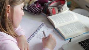 Κορίτσι που κάνει τη γραπτή εργασία στην κρεβατοκάμαρα απόθεμα βίντεο