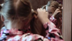 Κορίτσι που κάνει τις πλεξίδες μπροστά από τον καθρέφτη απόθεμα βίντεο