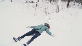 Κορίτσι που κάνει τον άγγελο στο χιόνι απόθεμα βίντεο