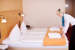 Κορίτσι που κάνει το κρεβάτι στο δωμάτιο ξενοδοχείου Στοκ εικόνες με δικαίωμα ελεύθερης χρήσης