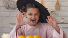 Κορίτσι που κάνει το τρομακτικό πρόσωπο στο κοστούμι μαγισσών που πηδά από κάτω από το κόμμα επιτραπέζιων αποκριών απόθεμα βίντεο