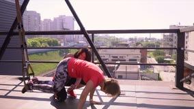 Κορίτσι που κάνει lunges με τους αλτήρες Το κορίτσι κάνει τις επιθέσεις στη γυμναστική σε ένα terassa οδών Αθλητική κατάρτιση φιλμ μικρού μήκους