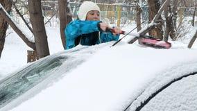 Κορίτσι που καθαρίζει το αυτοκίνητό της από το χιόνι απόθεμα βίντεο