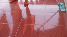Κορίτσι που καθαρίζει το κόκκινο πάτωμα κεραμιδιών με την μπλε σφουγγαρίστρα microfiber απόθεμα βίντεο