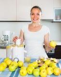 Κορίτσι που κατασκευάζει το χυμό από τα μήλα Στοκ Εικόνες