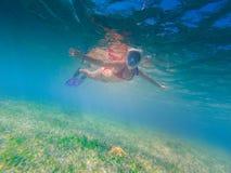 Κορίτσι που κολυμπά με αναπνευτήρα σε μια όμορφη αφθονία λιμνοθαλασσών των ψαριών Στοκ Φωτογραφία