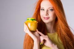 Κορίτσι που κρατά ένα βάζο του μελιού στοκ φωτογραφία