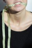 Κορίτσι που κρατά ένα εκατοστόμετρο στο στόμα της Στοκ εικόνες με δικαίωμα ελεύθερης χρήσης