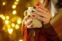 Κορίτσι που κρατά ένα καυτό φλυτζάνι του τσαγιού Στοκ Φωτογραφία