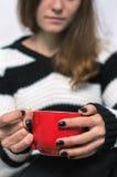 Κορίτσι που κρατά ένα κόκκινο φλυτζάνι του τσαγιού Στοκ εικόνες με δικαίωμα ελεύθερης χρήσης