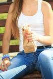 Κορίτσι που κρατά ένα πλαστικό μπουκάλι σε μια τσάντα εγγράφου στοκ φωτογραφία