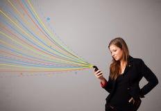 Κορίτσι που κρατά ένα τηλέφωνο με τις ζωηρόχρωμες αφηρημένες γραμμές Στοκ φωτογραφία με δικαίωμα ελεύθερης χρήσης