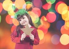 Κορίτσι που κρατά ένα χρυσό αστέρι Χριστουγέννων Στοκ Εικόνες