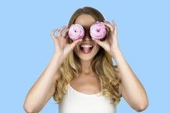 Κορίτσι που κρατά δύο cupcakes κοντά απομονωμένο στο πρόσωπο μπλε υπόβαθρό της στοκ φωτογραφία