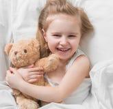 Κορίτσι που κρατά καφετή teddy της, στο κρεβάτι Στοκ φωτογραφία με δικαίωμα ελεύθερης χρήσης