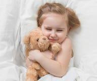 Κορίτσι που κρατά καφετή teddy της, στο κρεβάτι Στοκ Φωτογραφίες