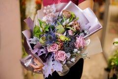 Κορίτσι που κρατά μια ανθοδέσμη των τριαντάφυλλων, των ξηρών παπαρουνών και των πορφυρών φύλλων Στοκ Φωτογραφίες