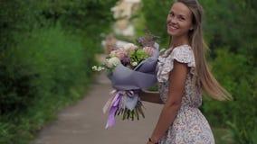 Κορίτσι που κρατά μια ανθοδέσμη των φρέσκων λουλουδιών στα χέρια της απόθεμα βίντεο