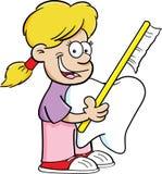 Κορίτσι που κρατά μια οδοντόβουρτσα και ένα δόντι Στοκ Φωτογραφία