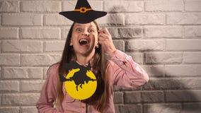 Κορίτσι που κρατά τα εμβλήματα με το καπέλο και τη μάγισσα Στοκ Εικόνα