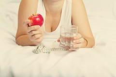 Κορίτσι που κρατά τη Apple και ένα ποτήρι του νερού Στοκ φωτογραφία με δικαίωμα ελεύθερης χρήσης
