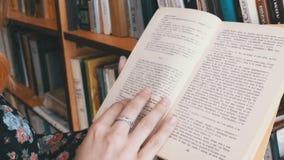 Κορίτσι που κρατά το βιβλίο στα χέρια και που διαβάζει στη βιβλιοθήκη στο υπόβαθρο των ραφιών απόθεμα βίντεο