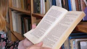 Κορίτσι που κρατά το βιβλίο στα χέρια και που διαβάζει στη βιβλιοθήκη στο υπόβαθρο των ραφιών φιλμ μικρού μήκους