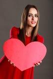 Κορίτσι που κρατά το κόκκινο σημάδι αγάπης καρδιών Στοκ φωτογραφίες με δικαίωμα ελεύθερης χρήσης