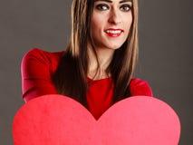 Κορίτσι που κρατά το κόκκινο σημάδι αγάπης καρδιών Στοκ Εικόνα