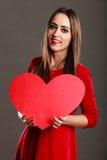 Κορίτσι που κρατά το κόκκινο σημάδι αγάπης καρδιών Στοκ Φωτογραφίες