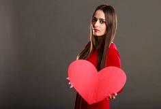 Κορίτσι που κρατά το κόκκινο σημάδι αγάπης καρδιών Στοκ Εικόνες