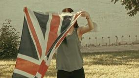Κορίτσι που κυματίζει το Union Jack στο αναδρομικό χρώμα φιλμ μικρού μήκους