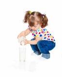 κορίτσι που λίγο γάλα χύνει στοκ φωτογραφίες