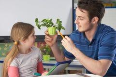 Κορίτσι που μαθαίνει για τα φυτά με το δάσκαλο στοκ φωτογραφία
