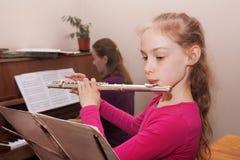 Κορίτσι που μαθαίνει να παίζει το φλάουτο στοκ εικόνες