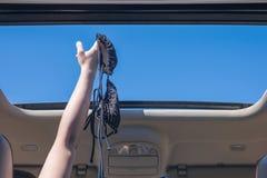 Κορίτσι που μακριά ο στηθόδεσμος μπικινιών της έξω από την ανοικτή πόρτα ενός οχήματος στοκ φωτογραφία με δικαίωμα ελεύθερης χρήσης