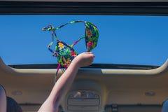 Κορίτσι που μακριά ο στηθόδεσμος μπικινιών της έξω από την ανοικτή πόρτα ενός οχήματος στοκ εικόνα