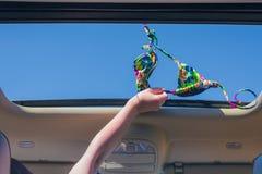 Κορίτσι που μακριά ο στηθόδεσμος μπικινιών της έξω από την ανοικτή πόρτα ενός οχήματος στοκ εικόνες με δικαίωμα ελεύθερης χρήσης