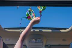 Κορίτσι που μακριά ο στηθόδεσμος μπικινιών της έξω από την ανοικτή πόρτα ενός οχήματος στοκ φωτογραφίες