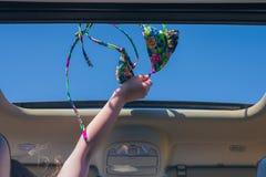 Κορίτσι που μακριά ο στηθόδεσμος μπικινιών της έξω από την ανοικτή πόρτα ενός οχήματος στοκ εικόνες